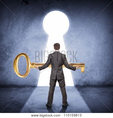 Businessman holding huge gold key, rear view
