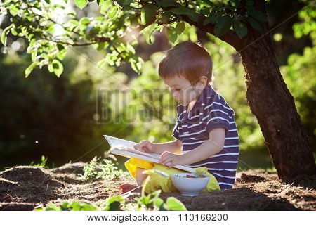 Beautiful Kid Boy, Reading A Book In Garden, Sitting Next To A Tree, Sunset Light