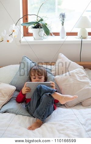 Adorable Cute Baby Boy, Playing On Tablet In Bed