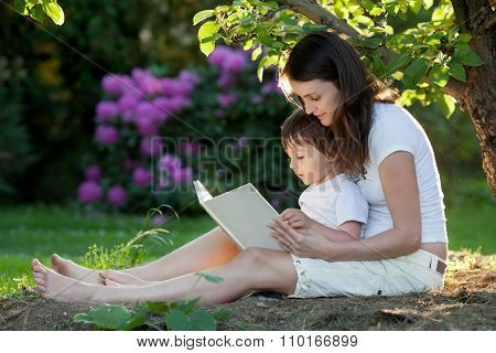 Mother And Boy, Reading A Book, Summertime In A Garden, Nice Sunset Light