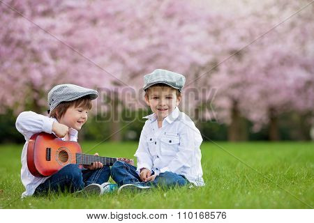 Two Adorable Caucasian Boys In A Blooming Cherry Tree Garden, Playing Guitar