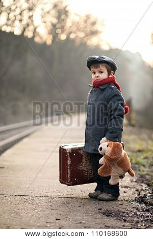 Portrait Of A Little Boy With S Suitcase And A Teddy Dog, Waiting On A Railway Station