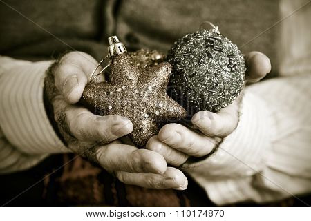 closeup of an old caucasian man with some christmas ornaments in his hands, in sepia toning