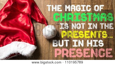 The Magic of Christmas Is Not In The Presents... But In His Presence written on wooden with Santa Hat
