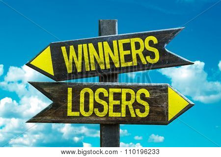 Winners - Losers signpost with sky background