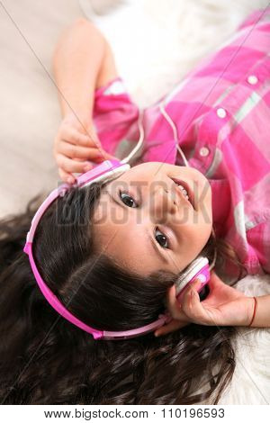 Smiling little girl listening music with pink headphones on the floor in light room, close up