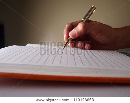 Hand holding a pen and writing on a notebook
