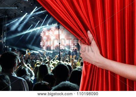 Human hand opens red curtain on concert scene background
