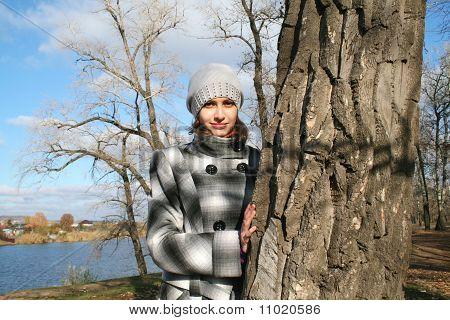 Молодая красивая девушка на дерево против голубое озеро