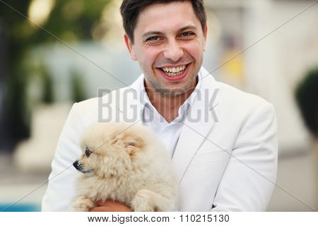 Happy Smiling Handsome Groom In White Suit Holding Dog Near Pool Closeup