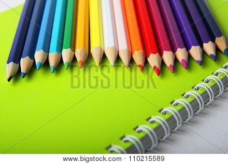 Bright Multicolor Pencils On Green Notebook