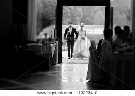 Black And White Happy Elegant Bride And Stylish Groom Entering Wedding Venue