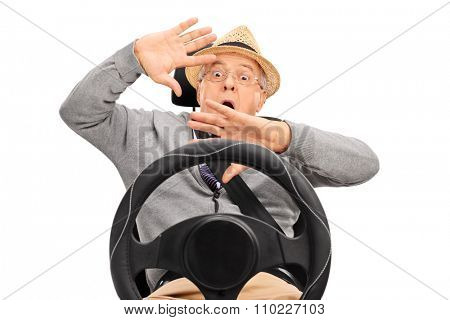 Scared senior man sitting on a car seat fastened with seatbelt and gesturing with his hands isolated on white background
