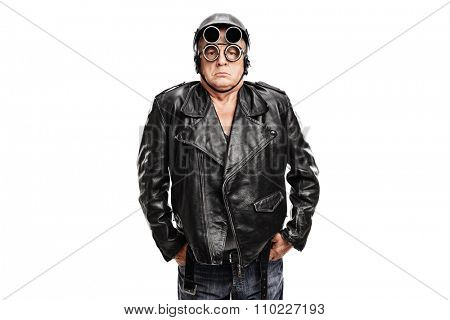 Grumpy mature motorcyclist posing in a black leather jacket with a helmet and goggles isolated on white background