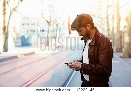 Glamorous male with cool style use smart phone during strolling outdoors