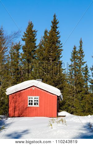 Typical Red Norwegian Cabin Surrounded By Snow In The Forest