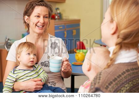 Mothers With Babies Chatting And Drinking Coffee At Playgroup