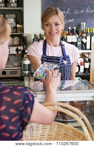Customer Paying For Shopping In Delicatessen Using Credit Card M