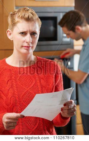 Worried Woman With Cooker Reapir Bill