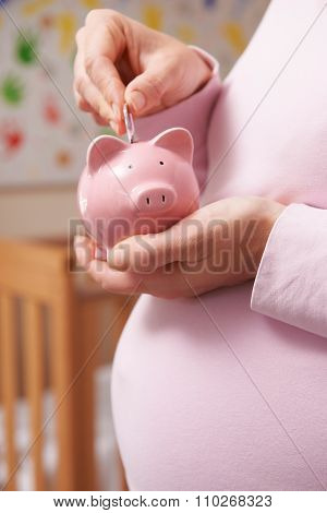 Pregnant Woman In Nursery Putting Money Into Piggy Bank