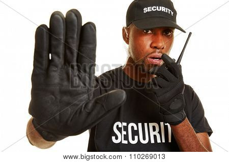 Man from security firm talking into radio set and keeping distance with his hand