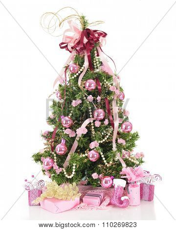 A beautiful, full Christmas tree decorated in pearls and pink  flowers, ribbons and shiny bulbs.  A lacy pink skirt and pretty pink-decorated gifts  surround the base.  On a white background.
