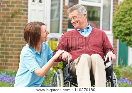 Carer Talking With Senior Man In Wheelchair poster