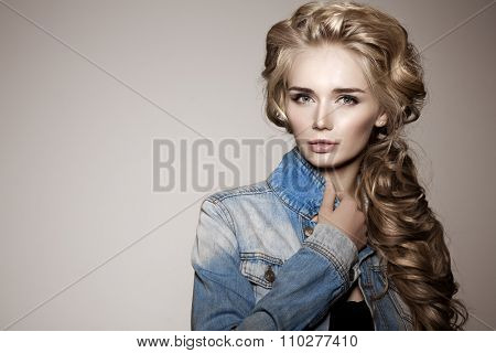 Model with long braided hair. Waves Curls Braid Hairstyle. Hair Salon. Updo. Fashion shiny hair. Woman with healthy hair, girl with luxurious haircut. Hair loss, braiding hair volume, jeans, denim.