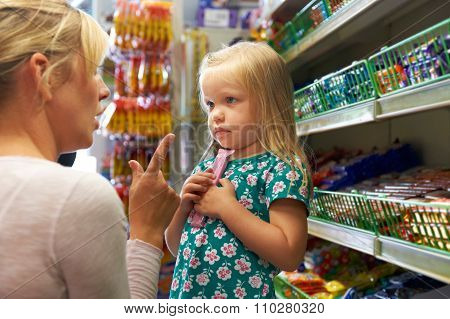 Girl Having Arguement With Mother At Candy Counter In Supermarke