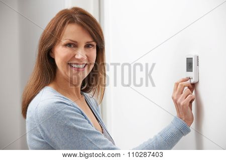 Smiling Woman Adjusting Thermostat On Home Heating System poster