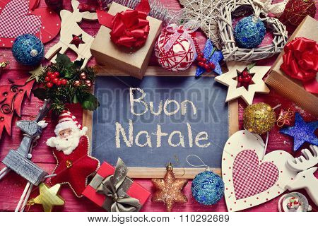high-angle shot of a chalkboard with the text buon natale, merry christmas in italian, surrounded by a pile of gifts and different bonnie christmas ornaments
