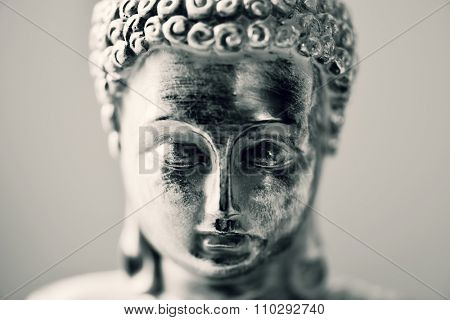 closeup of the face of a representation of the buddha in duotone