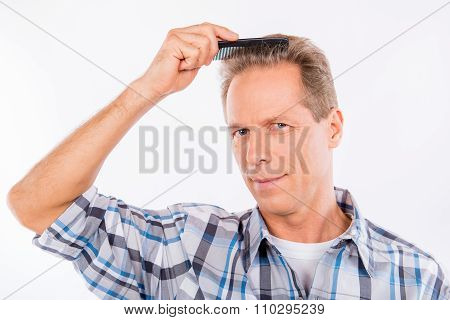 Handsome Keen Aged Man Combing His Hair