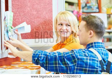 Sales assistant at work. smiling female hardware store worker helps to choose paint for painting to buyer customer with color samles during shopping