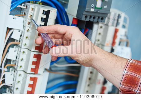 electrician hand with electric test screwdriver checking voltage of switching electric actuator equipment in fuse box