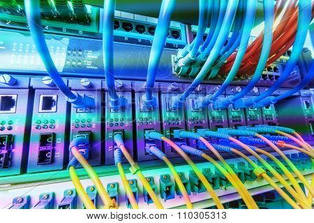 cables connected to an optic ports and UTP Network cables connected to ethernet ports.