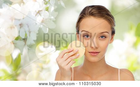 beauty, people, toiletry and skincare concept - young woman cleaning face with exfoliating sponge over cherry blossom background poster