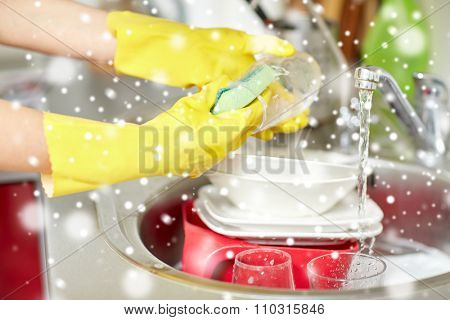 people, housework, washing-up and housekeeping concept - close up of woman hands in protective gloves washing dishes with sponge at home kitchen over snow effect