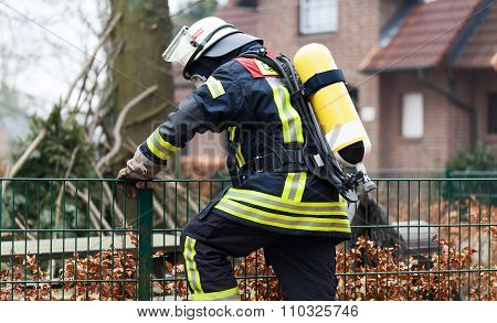 Fireman with breathing apparatus and oxygen cylinder in use