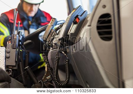 Fireman in the fire truck with radio set