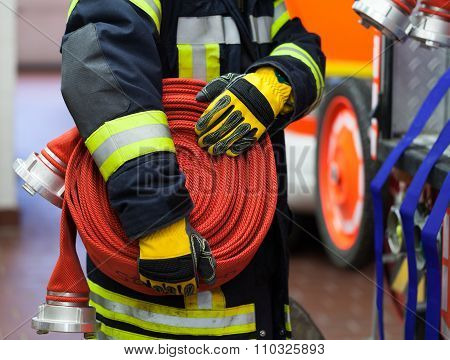 A firefighter wearing a rolled fire hose in hand