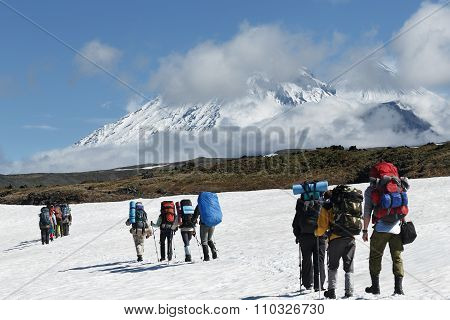 Hikers Group Trekking In Mountains On Background Of Volcanoes