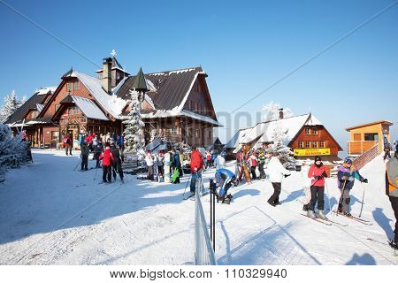 KOHUTKA SKI RESORT, CZECH REPUBLIC - JANUARY 16, 2010: Ski resort in the Czech Tatra. Houses with peaked roofs. Frosty sunny winter day. Skiers in bright jackets are preparing to skiing