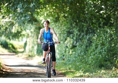 Middle Aged Woman Cycling On Country Road
