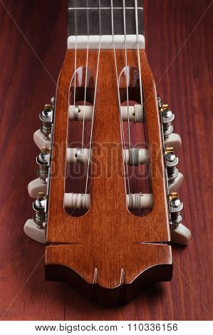 Guitar headstock viewed from low angle on wooden board focused on nearest tuners