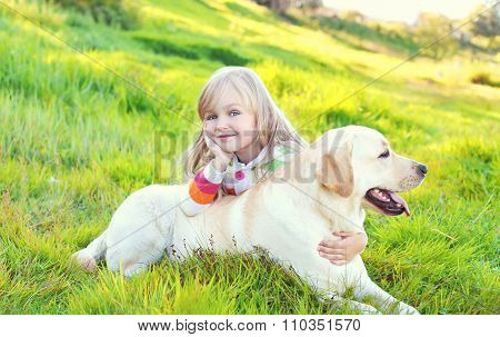 Happy Child And Labrador Retriever Dog Lying On Grass In Summer Day