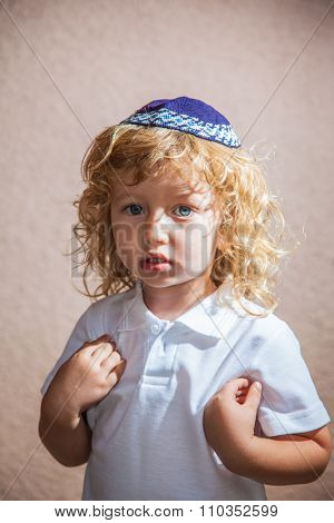 The charming little boy with long blond curls and blue eyes in Jewish knitted kippah