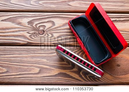 Harmonica Next To The Packaging On The Wooden Background