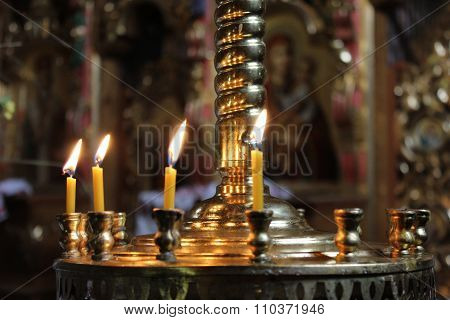 Candles light on chandelier in ancient Orthodox church