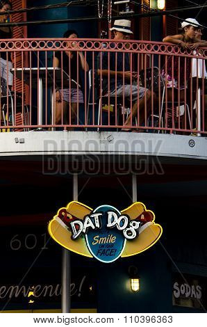 Dat Dog restaurant sign with people eating at the background.